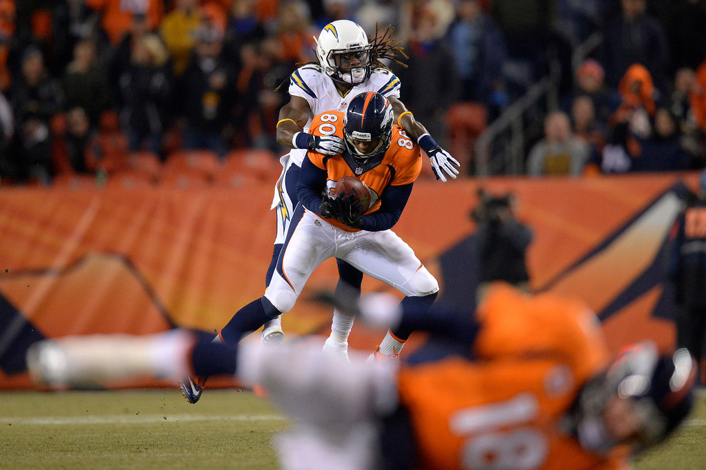 . Denver Broncos tight end Julius Thomas (80) makes a catch while defended by San Diego Chargers defensive back Jahleel Addae (37) as Denver Broncos quarterback Peyton Manning (18) is knocked to the ground during the first quarter  The Denver Broncos vs. the San Diego Chargers at Sports Authority Field at Mile High in Denver on December 12, 2013. (Photo by John Leyba/The Denver Post)