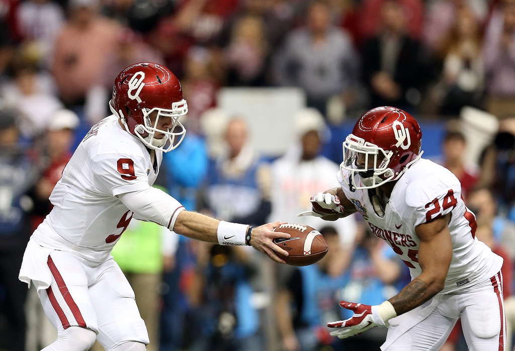 . NEW ORLEANS, LA - JANUARY 02: Trevor Knight #9 of the Oklahoma Sooners hands the ball off to Brennan Clay #24 against the Alabama Crimson Tide during the Allstate Sugar Bowl at the Mercedes-Benz Superdome on January 2, 2014 in New Orleans, Louisiana.  (Photo by Sean Gardner/Getty Images)