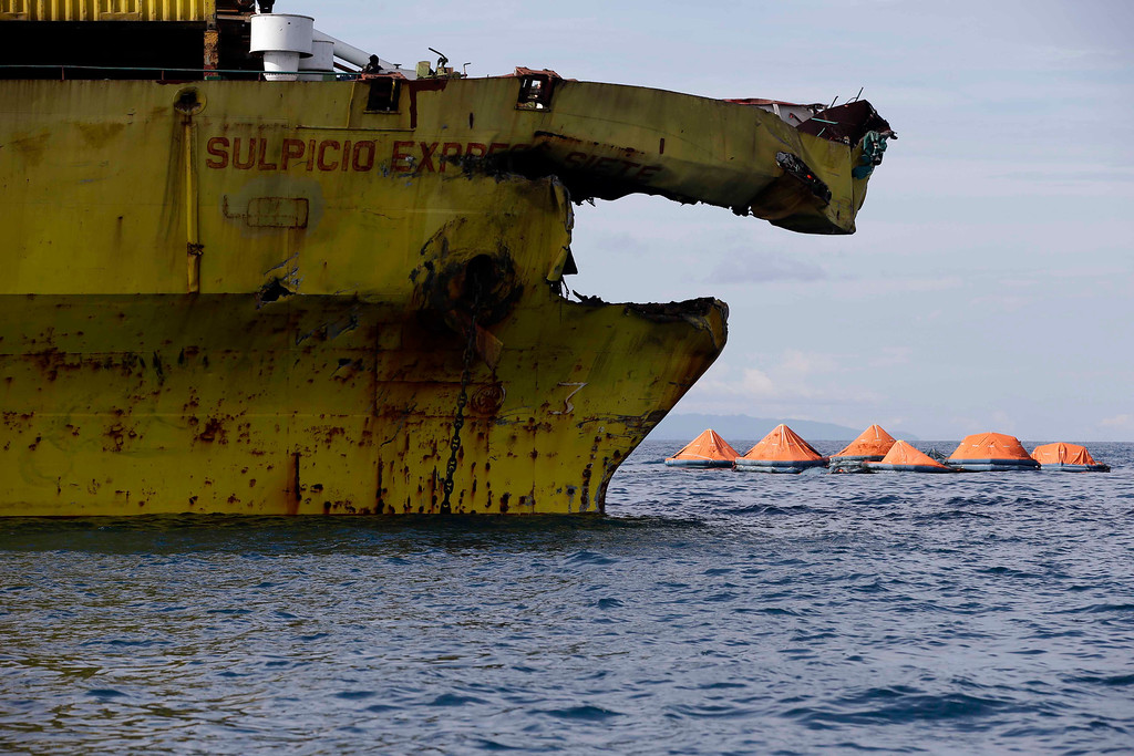 . A cluster of life rafts ifloat near the damaged cargo ship Sulpicio Express Siete Saturday Aug. 17, 2013, a day after it collided with a passenger ferry off the waters of Talisay city, Cebu province in central Philippines. Divers combed through a sunken ferry Saturday to retrieve the bodies of more than 200 people still missing from an overnight collision with a cargo vessel near the central Philippine port of Cebu that sent passengers jumping into the ocean and leaving many others trapped. At least 28 were confirmed dead and hundreds rescued. The captain of the ferry MV Thomas Aquinas, which was approaching the port late Friday, ordered the ship abandoned when it began listing and then sank just minutes after collision with the MV Sulpicio Express, coast guard deputy chief Rear Adm. Luis Tuason said. (AP Photo/Bullit Marquez)