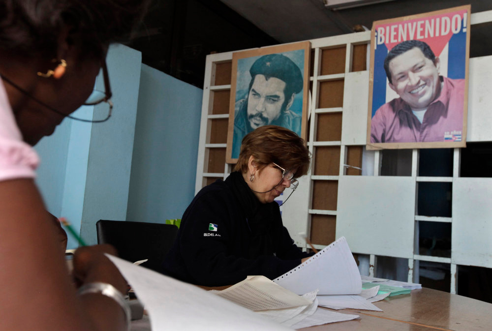 . Election officials sit at a table near pictures of Latin American revolutionary Ernesto Che Guevara (L) and Venezuela\'s President Hugo Chavez in Havana February 3, 2013. Cubans went to the polls on Sunday to elect a Communist Party selected slate of 612 deputies to the National Assembly, at a time of change in how they live and work, but not in how they vote. REUTERS/Enrique De La Osa