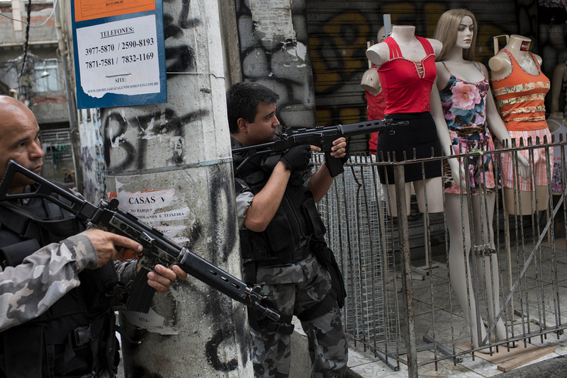 """. Military police officer patrol during an occupation operation of the Mare slum complex, ahead of its \""""pacification,\"""" in Rio de Janeiro, Brazil, Tuesday, March 25, 2014. (AP Photo/Felipe Dana)"""