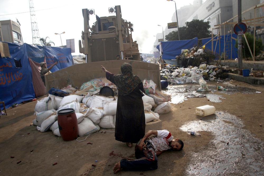 . An Egyptian woman tries to stop a military bulldozer from hurting a wounded youth during clashes that broke out as Egyptian security forces moved in to disperse supporters of Egypt\'s deposed president Mohamed Morsi in a huge protest camp near Rabaa al-Adawiya mosque in eastern Cairo on August 14, 2013. The operation began shortly after dawn when security forces surrounded the sprawling Rabaa al-Adawiya camp in east Cairo and a similar one at Al-Nahda square, in the centre of the capital, launching a long-threatened crackdown that left dozens dead.  MOHAMMED ABDEL MONEIM/AFP/Getty Images