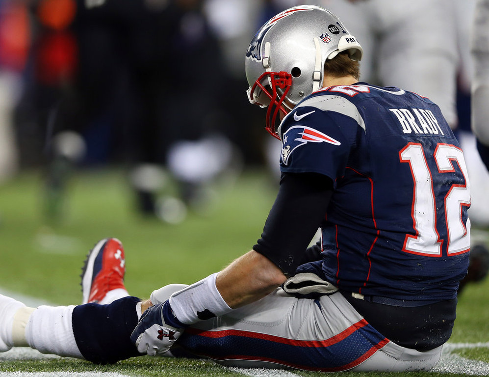 . Tom Brady #12 of the New England Patriots sits on the ground after getting knocked down in the fourth quarter against the Baltimore Ravens during the 2013 AFC Championship game at Gillette Stadium on January 20, 2013 in Foxboro, Massachusetts.  (Photo by Elsa/Getty Images)