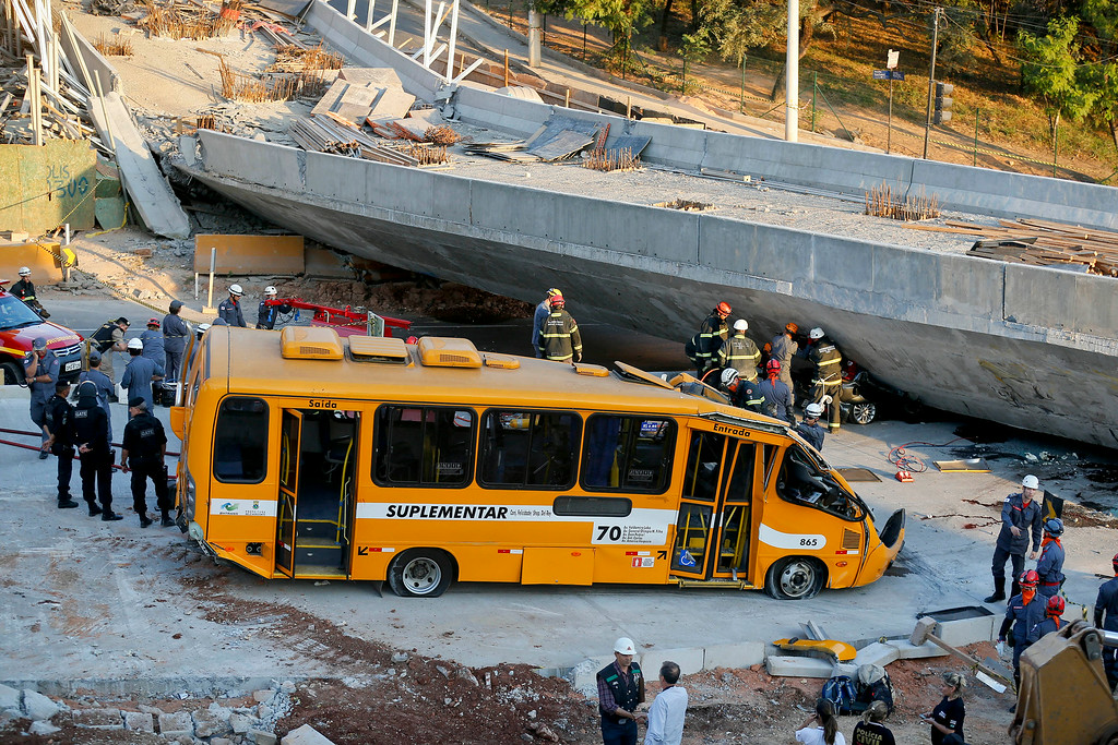 . A bus sits damaged after a bridge collapsed in Belo Horizonte, Brazil, Thursday, July 3, 2014. The overpass under construction collapsed Thursday in the Brazilian World Cup host city. The incident took place on a main avenue, the expansion of which was part of the World Cup infrastructure plan but, like most urban mobility projects related to the Cup, was not finished on time for the event. (AP Photo/Victor R. Caivano)