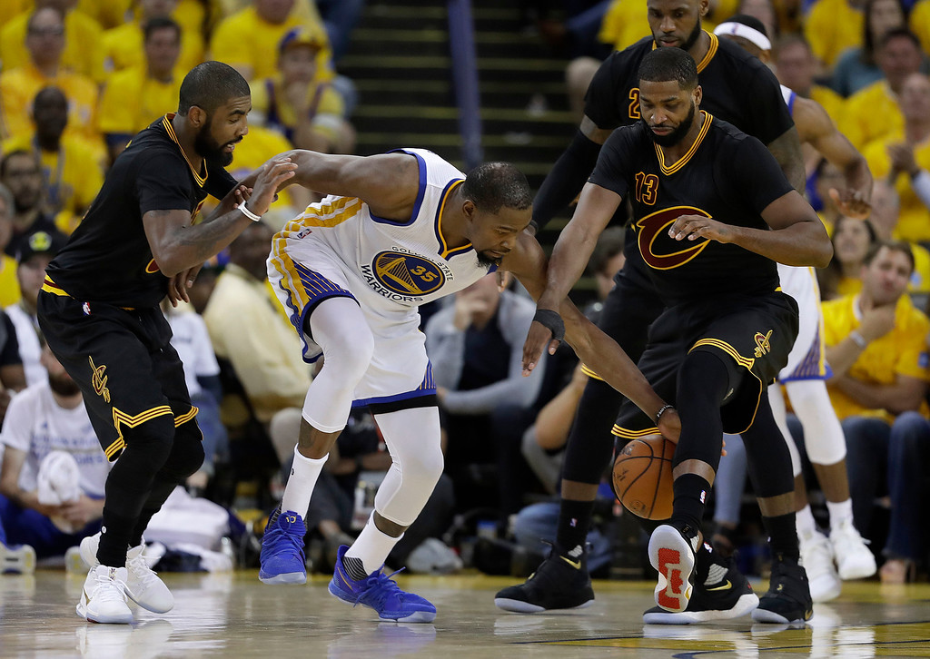 . Golden State Warriors forward Kevin Durant (35) reaches for the ball between Cleveland Cavaliers guard Kyrie Irving, left, and center Tristan Thompson (13) during the second half of Game 2 of basketball\'s NBA Finals in Oakland, Calif., Sunday, June 4, 2017. (AP Photo/Marcio Jose Sanchez)