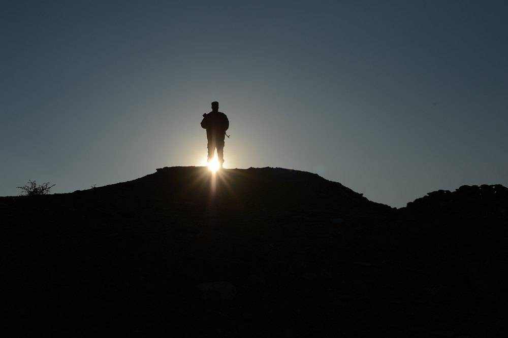 Description of . An Afghan commando force stand guard at sunset in Goshti district of Nangarhar province, bordering  Pakistan on December 18, 2012.The Afghan security forces, which did not exist until the Taliban fell in 2001, have been built up quickly and still lack professionalism. According to a recent Pentagon report, Afghans have