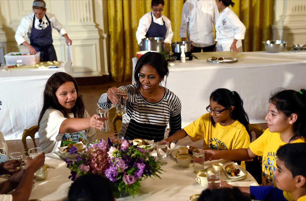 . First lady Michelle Obama offers a toast as she sits with school children as they eat lunch in the East Room of the White House following the annual fall harvest of the White House Kitchen Garden in Washington, Tuesday, Oct. 14, 2014. (AP Photo/Susan Walsh)