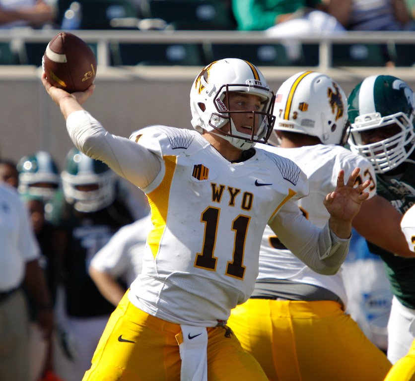 . Wyoming quarterback Colby Kirkegaard (11) throws a pass during the fourth quarter of an NCAA college football game against Michigan State, Saturday, Sept. 27, 2014, in East Lansing, Mich. Michigan State won 56-14. (AP Photo/Al Goldis)
