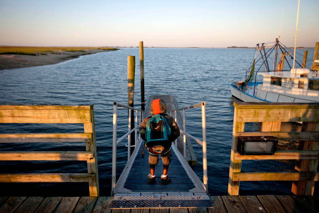 . Jonathan Wilson, 6, stands on the dock before boarding a ferry from his home in the Hog Hammock community of Sapelo Island, Ga. to the mainland to attend school on Wednesday, May 15, 2013. (AP Photo/David Goldman)