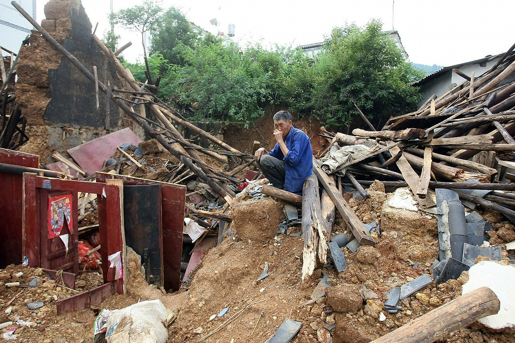 . A man reacts in front of his collapsed house at the quake-hit area on August 4, 2014 in Zhaotong, China. A 6.5-magnitude earthquake hit Zhaotong\'s Ludian county on August 3, killing at least 410 people.  (Photo by ChinaFotoPress/ChinaFotoPress via Getty Images)