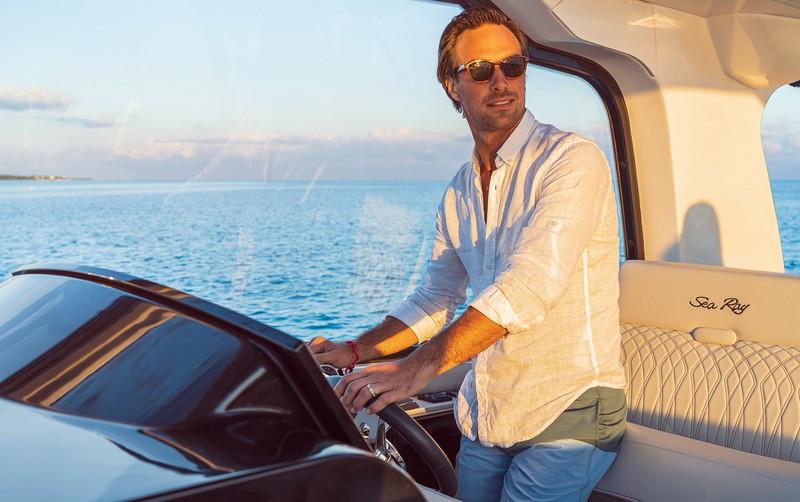 2021-Sundancer-370-Outboard-DAO370-lifestyle-man-helm-06014-select.jpg