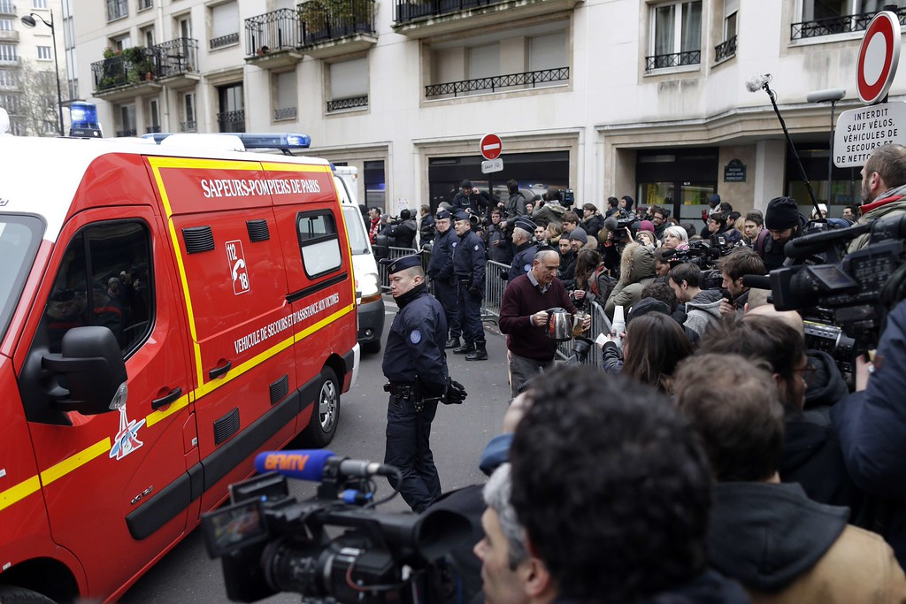 . Firefighters and policemen are surrounded by journalistsM outside of the headquarters of the French satirical newspaper Charlie Hebdo in Paris on January 7, 2015, after armed gunmen stormed the offices leaving twekve dead. Heavily armed gunmen shouting Islamist slogans stormed a Paris satirical newspaper office on January 7 and shot dead at least 12 people in the deadliest attack in France in four decades. Police launched a massive manhunt for the masked attackers who reportedly hijacked a car and sped off, running over a pedestrian and shooting at officers.     AFP PHOTO / KENZO  TRIBOUILLARD/AFP/Getty Images