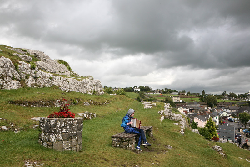 A young musician plays outside of The Rock of Cashel, Ireland.