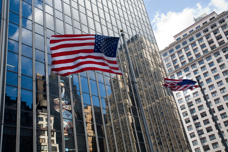 American flags and glass buildings on 34th street, NYC, USA