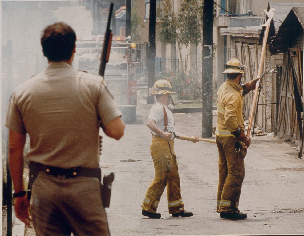 . A California Highway Patrolman stands guard as firefighters mop up a fire in Korea Town. Firefighters were coming under attack by people in the days after the initial riots broke out. April 30, 1992 . (Photo by John McCoy/Los Angeles Daily News).