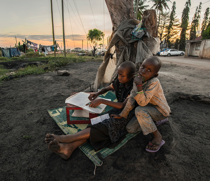 Two kids doing their  homework out in the street.  Dar es Salam, Tanzania, 2019