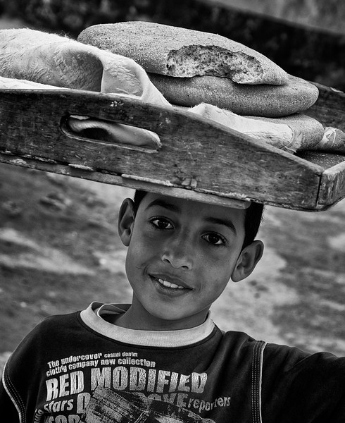 Boy fetching bread from the local wood burning oven. When we met him he had already fallen into the temptation of taking a bite of the freshly made, flat bread. In Moroccan towns most people dont own an oven,  so locals take their dough to the communal oven and have it baked by the baker for a small fee. 