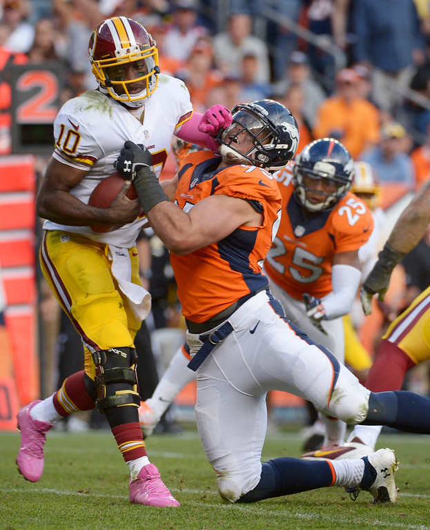 . Denver Broncos defensive end Derek Wolfe (95) gets a hold of Washington Redskins quarterback Robert Griffin III (10) for a sack during the fourth quarter. The Denver Broncos vs. the Washington Redskins at Sports Authority Field at Mile High in Denver on October 27, 2013. (Photo by Tim Rasmussen/The Denver Post)