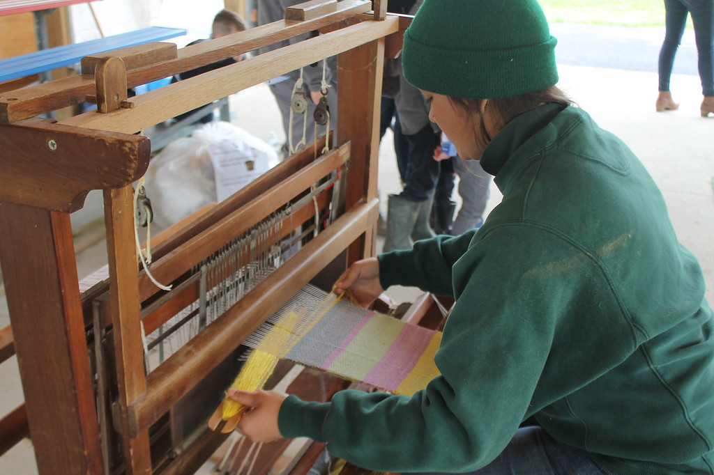 . Kelly Mader, Farmpark interpreter demonstrates weaving yarn on a loom during the Farmpark\'s sheep shearing weekend on May 13.  The yarn been used is made from fleece sheared off a sheep that had been dyed with Kool-aid and water. Kristi Garabrandt - The News-Herald