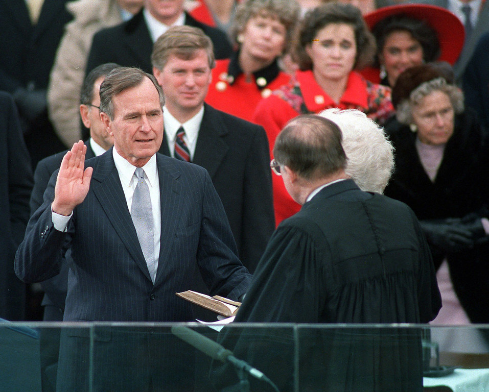. President George Bush raises his hand on Jan. 20,1989 as he takes the oath of office as president of the United States outside the Capitol. Vice President Dan Quayle watches from behind. (AP Photo/Ron Edmonds)