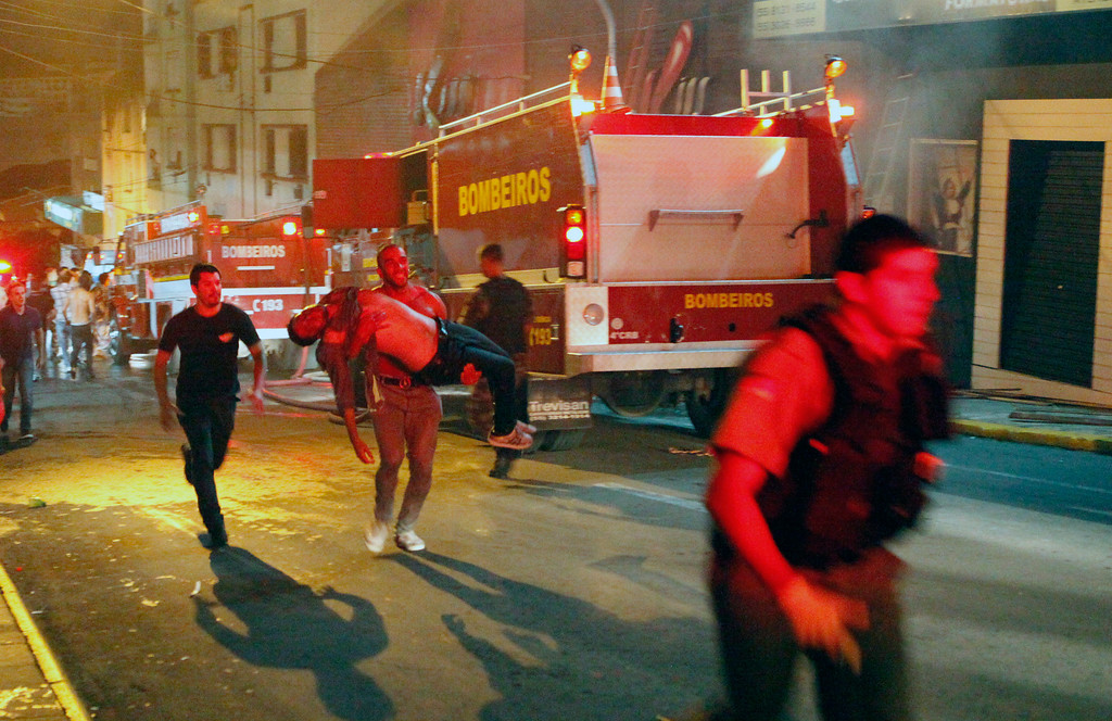 . A man carries an injured victim of a fire at the Kiss  club in Santa Maria city,  Rio Grande do Sul state,  Brazil, early Sunday, Jan. 27, 2013.   (AP Photo/Agencia RBS)