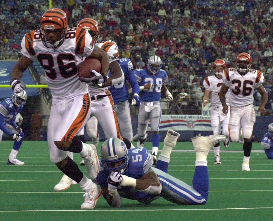 . Barrett Green (54) of the Detroit Lions tries to bring down Darnay Scott of the Cincinnati Bengals before he scored a touchdown during Sunday\'s game played at the Pontiac Silverdome. The Lions lost 31-27 to the Bengals.