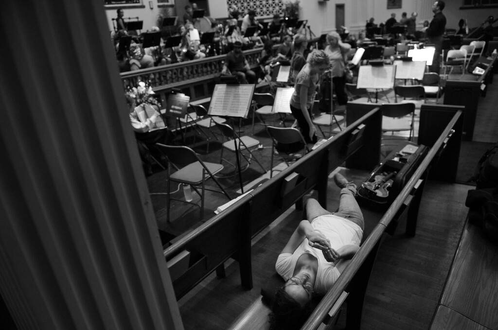 """. Violinist Emmy Reid rests in a pew during a rehearsal break with the Denver Philharmonic Orchestra at the KPOF Concert Hall in Denver, CO, Monday September 24, 2012.  Besides being a \""""stay-at-home mom\"""" Reid, 32, works a 12-hour shift, once a week, as a surgery scheduler at Swedish Hospital. She later explained, \""""I was lying down because I had been working all day, I worked 7 to 7. Then I had half an hour to get downtown and get in there and start playing the violin.\"""" \""""I started playing violin when I was 11, in elementary school,\"""" she recalled.  She continued to play in orchestras throughout middle school, high school and college, \""""then after college I kind of missed it.\""""  Reid is now in her sixth season. \""""I go to work, I go home, I\'m a mom, I cook dinner, I take care of my husband. This is a chance for me to do something for myself... It\'s a wonderful, lifelong hobby and you can see that in the ages in the orchestra. There\'s young and old.\"""" She says music also keeps her connected to the past, \""""I\'ve always felt that music has the ability to transport a person... My family always listened to classical music. Being in the middle of music and being part of the music brings back memories of when my father was alive... It brings back parts of my life that are gone forever.\"""" Craig F. Walker, The Denver Post"""