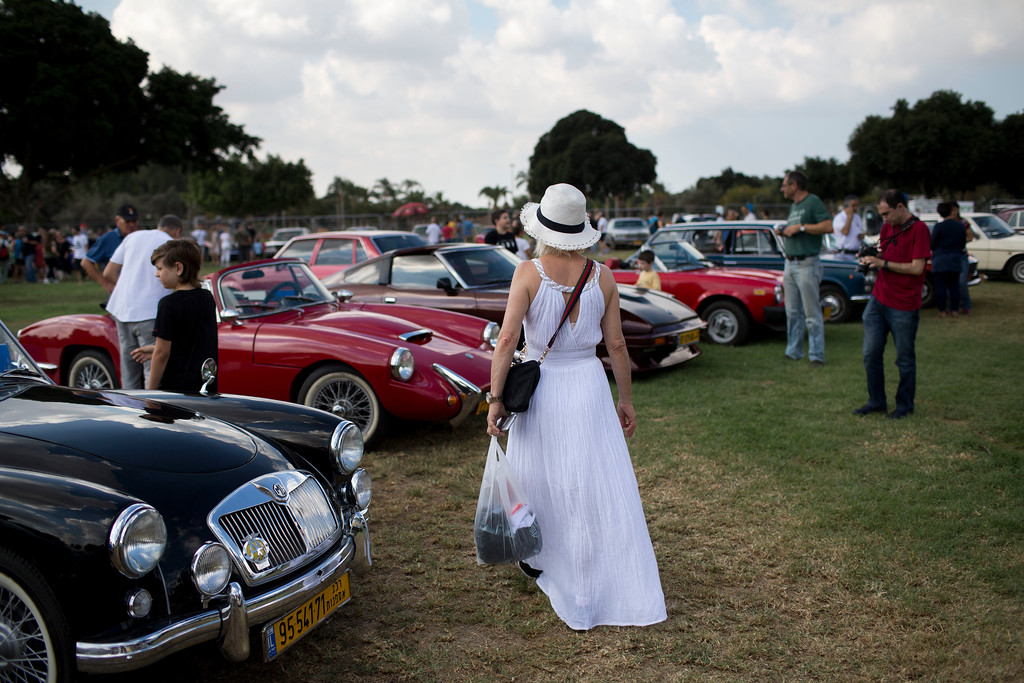 ". People look at antique cars during the 31st annual ""Five Club\"" car collectors\' meeting in Ramat Gan, Israel, Friday, Oct. 6, 2017. Each weekend, at Israeli gas stations and parking lots and parks, car collectors gather with their beauties _ and take a step back in time. (AP Photo/Oded Balilty)"