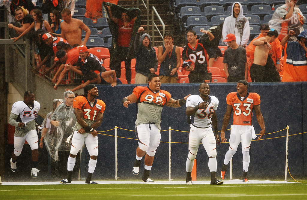 . DENVER, CO. - August 03: From right, Duke Ihenacho (33), Montee Ball (38), Sealver Sillga (98), Omar Bolden (31) and C.J.Anderson (39) are in the field to see the fans waiting scrimmage in the rain at Sports Authority Field at Mile High. Denver, Colorado. August 03, 2013. (Photo By Hyoung Chang/The Denver Post)