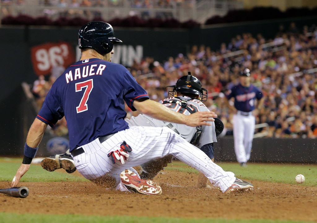. Minnesota Twins\' Joe Mauer, left, scores on Trevor Plouffe fielder\'s choice as Detroit Tigers catcher Bryan Holaday, right, dives in vain for the wide throw in the sixth  inning of a baseball game, Friday, Aug. 22, 2014, in Minneapolis. (AP Photo/Jim Mone)