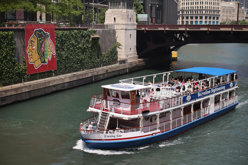 . A tour boat passes by a Chicago Blackhawks\' banner on the Chicago River in the Loop on June 12, 2013 in Chicago, Illinois. The Chicago Blackhawks will match up against the Boston Bruins tonight at the United Center in the first game on the NHL Stanley Cup playoffs.  (Photo by Scott Olson/Getty Images)
