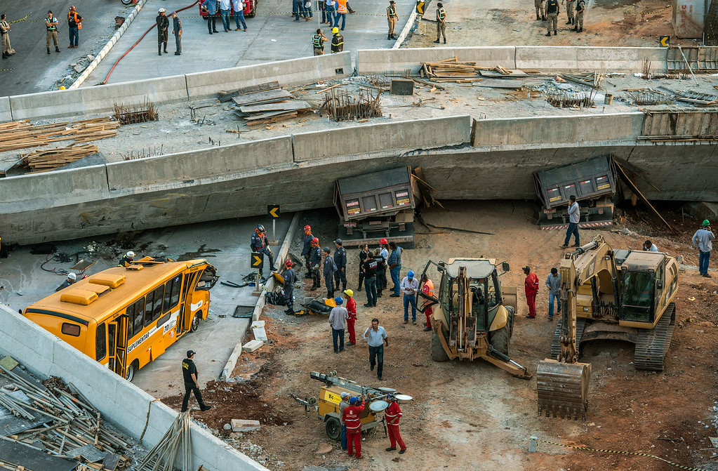 . Firefighters and policemen work at the site where a bus and trucks were crushed by a viaduct that collapsed in Belo Horizonte, Brazil, on July 3, 2014. An unfinished overpass collapsed on vehicles in Brazil\'s southeastern World Cup city of Belo Horizonte on Thursday, killing at least two people and injuring 19, officials said. AFP PHOTO/PEDRO DUARTE/AFP/Getty Images