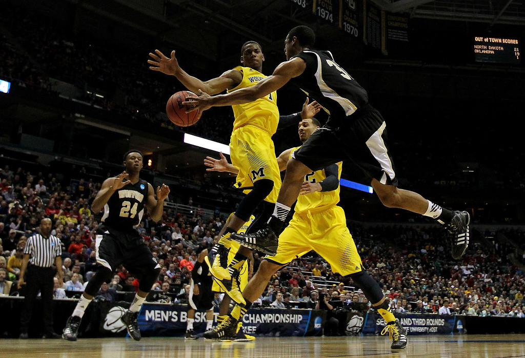 . Spencer Collins #32 of the Wofford Terriers passes around Glenn Robinson III #1 of the Michigan Wolverines in the second half during the second round of the 2014 NCAA Men\'s Basketball Tournament at BMO Harris Bradley Center on March 20, 2014 in Milwaukee, Wisconsin.  (Photo by Jonathan Daniel/Getty Images)