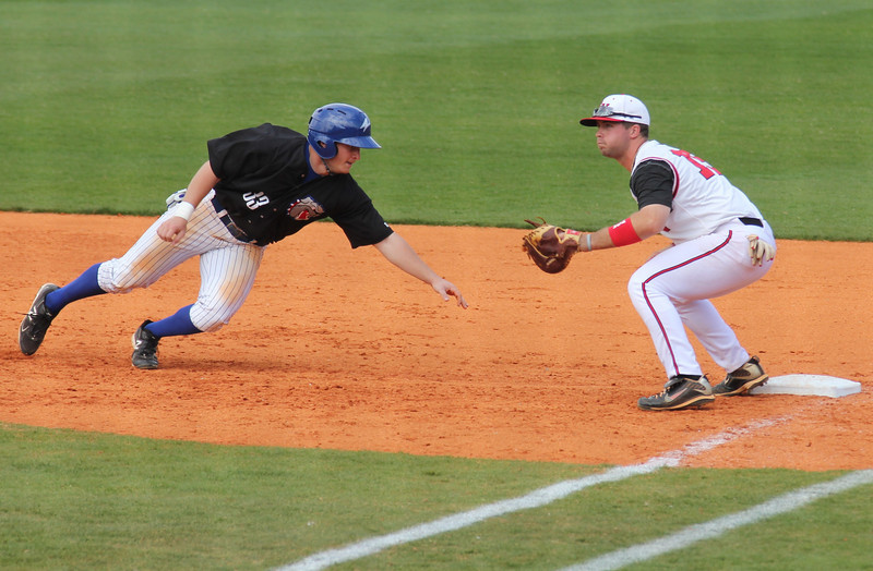 #15 Dusty Quattlebaum awaits a throw to first for an attempt to throw out the runner from UNC-Asheville.