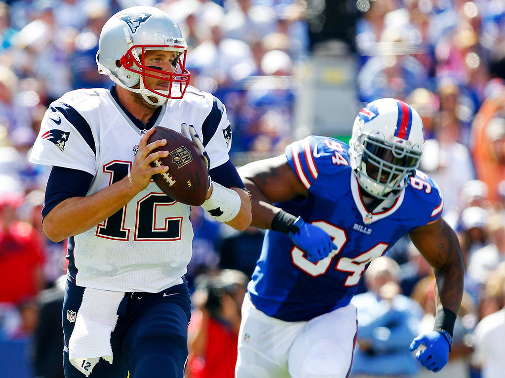 . New England Patriots\' Tom Brady (12) looks to pass as Buffalo Bills defensive end Mario Williams (94) closes in during the first half of an NFL football game on Sunday, Sept. 8, 2013, in Orchard Park. (AP Photo/Bill Wippert)