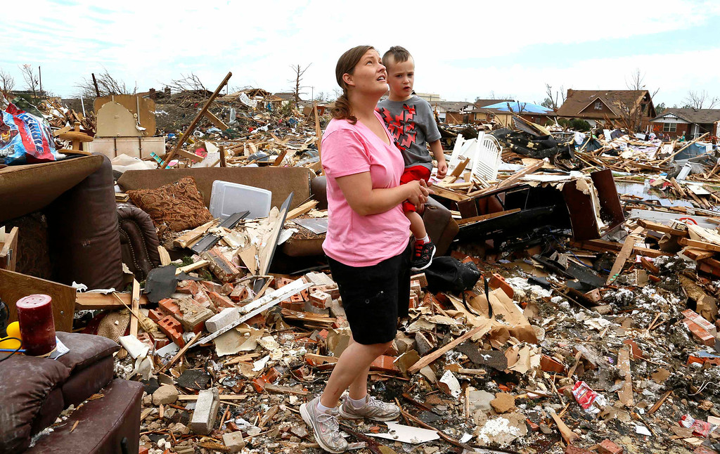 . Tracy Stephan, holding her son Timothy, 3, looks at her tornado-destroyed home on 6th Avenue in Moore, Oklahoma May 23, 2013. The tornado was the strongest in the United States in nearly two years and cut a path of destruction 17 miles long and 1.3 miles wide. REUTERS/Rick Wilking