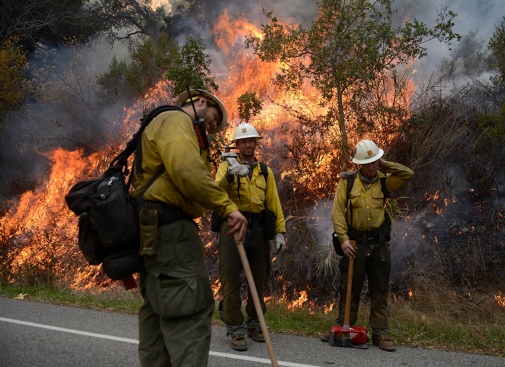 . Firefighters light a back fire along Highway 1 between Pfeiffer Ridge Road and the Big Sur Station in Big Sur, Calif. on Wednesday, December 18, 2013. (Photo David Royal/ Monterey County Herald)