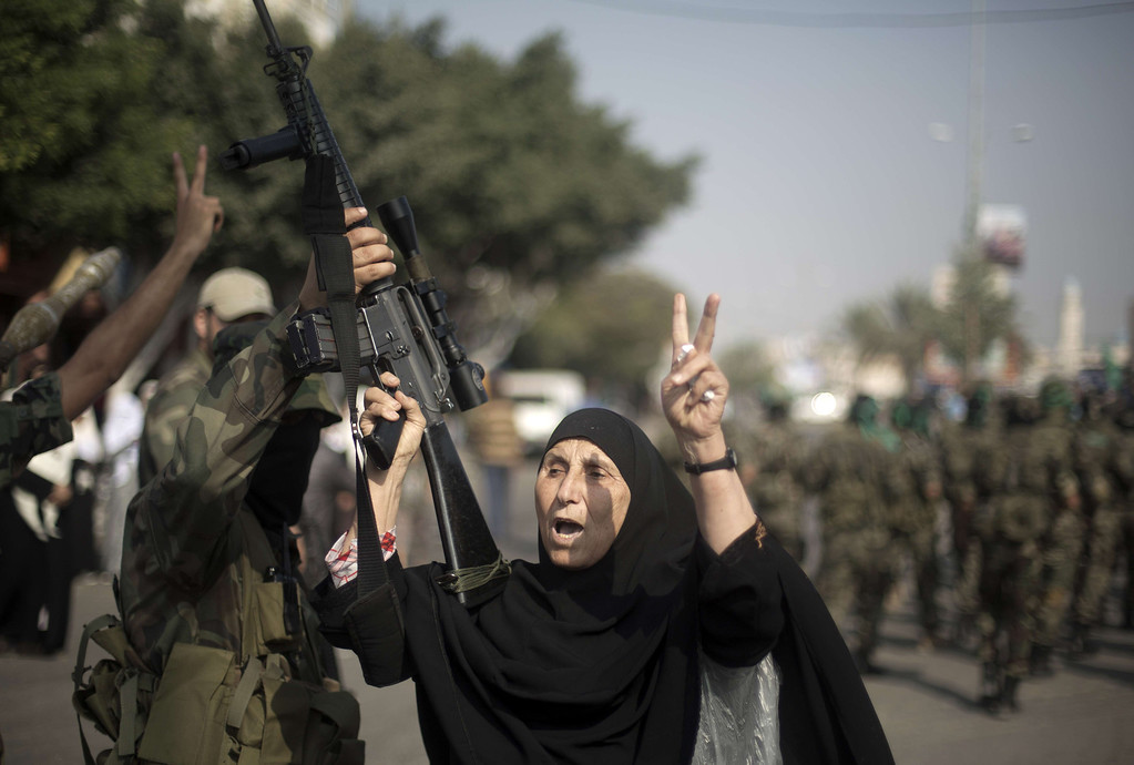 ". A Palestinian woman holds up a machine gun belonging to a masked militant of Ezzedine al-Qassam Brigades, Hamas\'s armed wing, as they parade in Jabalia refugee camp, northern Gaza Strip, on November 14, 2013, during an anti-Israel march as part of the celebrations marking the first anniversary of what Israel named the ""Pillar of Defense\"" Operation. AFP PHOTO/MOHAMMED  ABED/AFP/Getty Images"