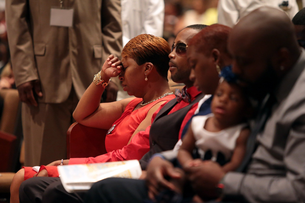 Description of . Lesley McSpadden, Michael Brown's mother, closes her eyes during the funeral services for her son on Monday, Aug. 25, 2014, at Friendly Temple Missionary Baptist Church in St. Louis. Hundreds of people gathered to say goodbye to Brown, who was shot and killed by a Ferguson, Mo., police officer on Aug. 9. (AP Photo/St. Louis Post Dispatch, Robert Cohen, Pool)