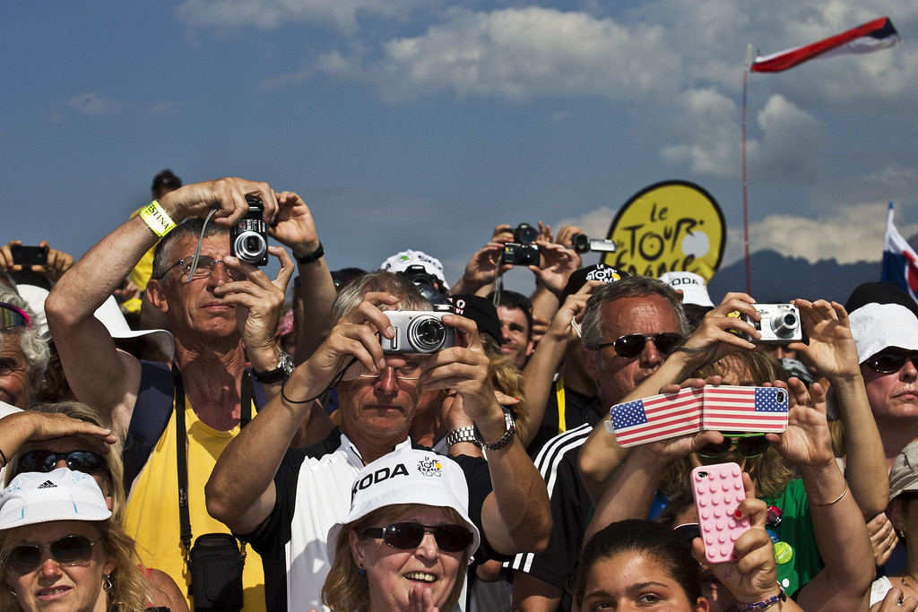 . Supporters take picture of riders during the 145.5 km third stage of the 100th edition of the Tour de France cycling race on July 1, 2013 between Ajaccio and Calvi, on the French Mediterranean Island of Corsica.   AFP PHOTO / JOEL SAGET/AFP/Getty Images