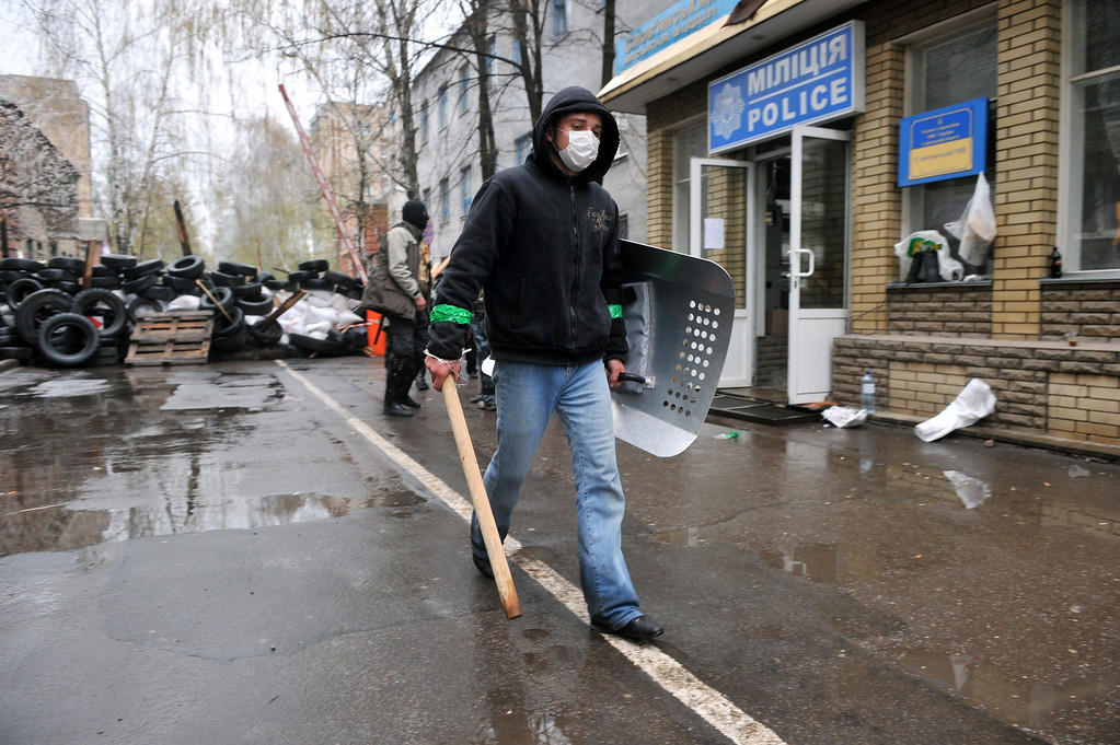 """. A pro-Russian activist, holding a wooden club and a shield, guards a barricade outside a regional police building seized by the armed separatists to prevent storming by the Ukrainian police special team in the eastern city of Slavyansk on April 13, 2014. Ukraine today launched an \""""anti-terrorist operation\"""" in Slavyansk, where pro-Russian gunmen have seized police and security services buildings, Interior Minister Arsen Avakov said. \""""Units from all of the country\'s force structures are participating. May God be with us,\"""" the minister wrote on his Facebook page. AFP PHOTO / GENYA SAVILOV"""