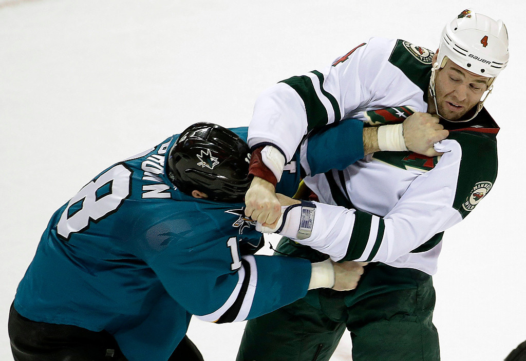 . Minnesota Wild\'s Clayton Stoner (4) fights with San Jose Sharks\' Mike Brown, left, during the first period of an NHL hockey game on Saturday, Jan. 25, 2014, in San Jose, Calif. (AP Photo/Marcio Jose Sanchez)