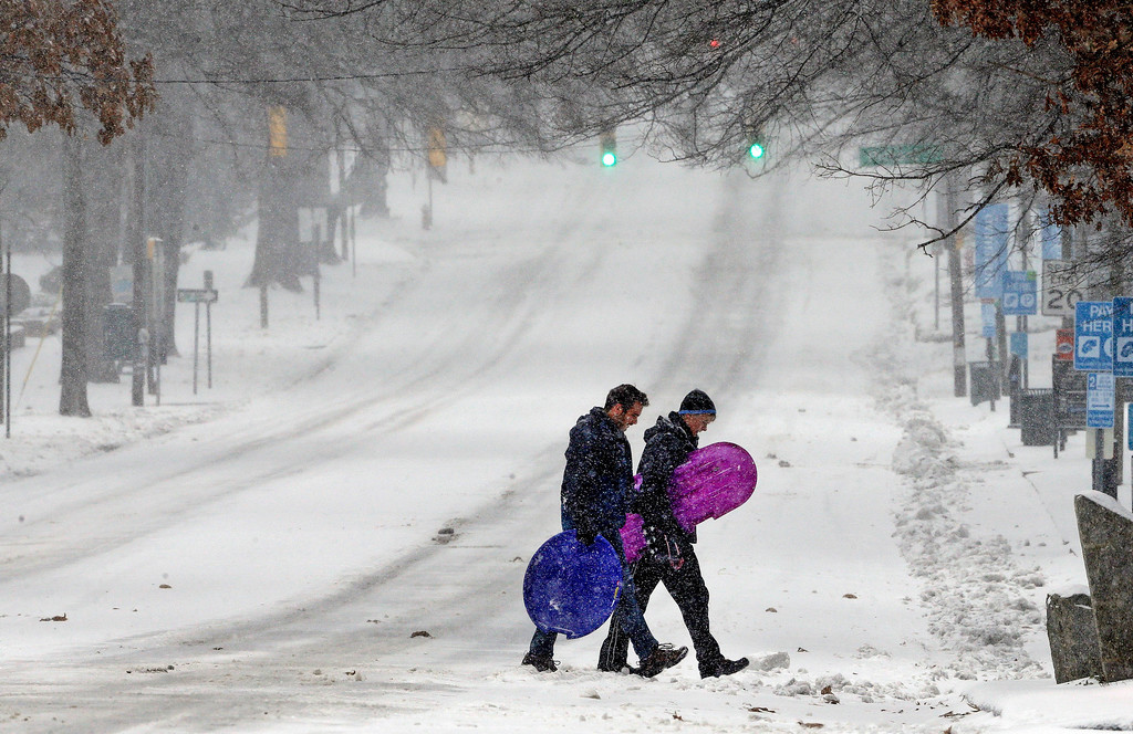 . Pedestrians cross a snowy Franklin Street in Chapel Hill, N.C., Saturday, Jan. 7, 2017 as a winter storm blankets the area with sleet and snow. (AP Photo/Gerry Broome)