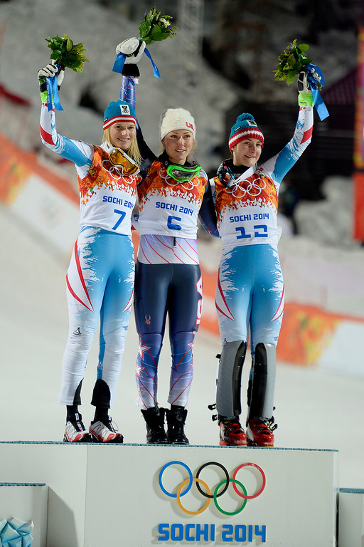 . Gold medalist American Mikaela Shiffrin raises her hands as she is announced while silver medalist Marlies Schild (left) and bronze medalist Kathrin Zettel (both of Austria) join after ladies\' slalom run 2. Sochi 2014 Winter Olympics on Friday, February 21, 2014 at Rosa Khutor Alpine Center. (Photo by AAron Ontiveroz/ The Denver Post)