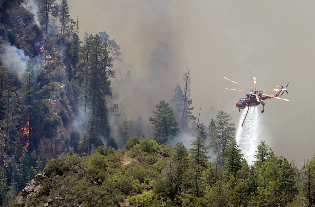 . A firefighting helicopter drops water on a forest fire in Oak Creak Canyon in Sedona, Ariz., on Thursday May 22, 2014. The human-caused Slide Fire started Tuesday and had burned 7 1/2 square miles in and around Oak Creek Canyon, a scenic recreation area along a highway between Sedona and Flagstaff that normally would be teeming with tourists as the Memorial Day weekend approaches. (AP Photo/ Vyto Starinskas)