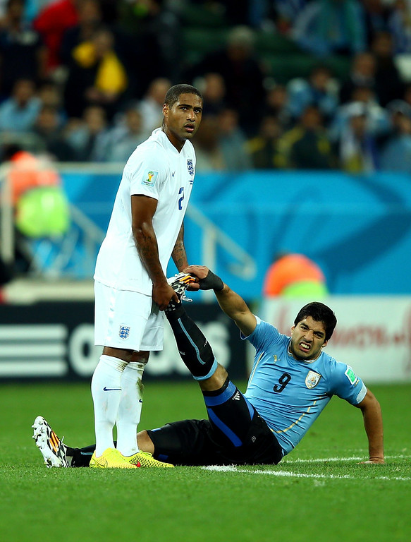 . Glen Johnson of England helps Luis Suarez of Uruguay stretch during the 2014 FIFA World Cup Brazil Group D match between Uruguay and England at Arena de Sao Paulo on June 19, 2014 in Sao Paulo, Brazil.  (Photo by Clive Rose/Getty Images)