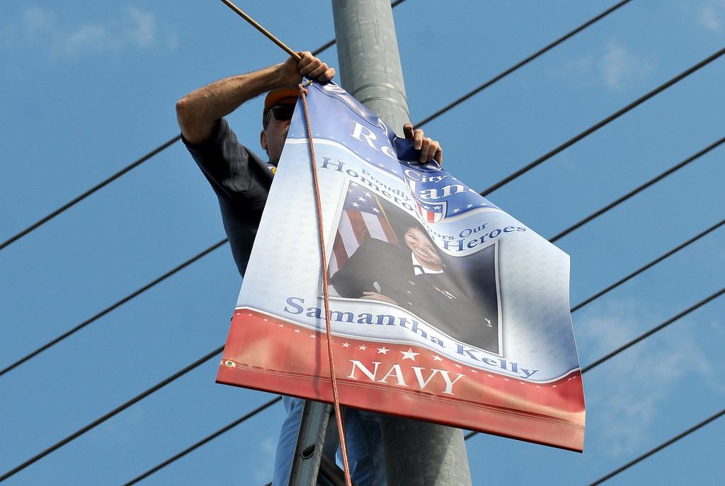. (John Valenzuela/Staff Photographer) Redlands Evening Kiwanis Club member Jerry Linkhart, hangs a Hometown Heroes banner for Redlands\' Naval officer Samantha Kelly, at the corner of New Jersey St. and Redlands Blvd., Tuesday, August 27, 2013. Kelly is a 2006 Redlands East Valley grad.