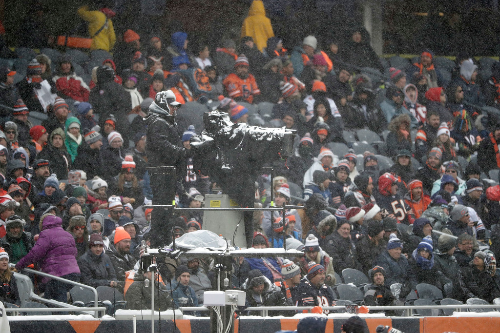. Snow collects on a cameraman in the first half of an NFL football game between the Chicago Bears and Cleveland Browns in Chicago, Sunday, Dec. 24, 2017. (AP Photo/Charles Rex Arbogast)