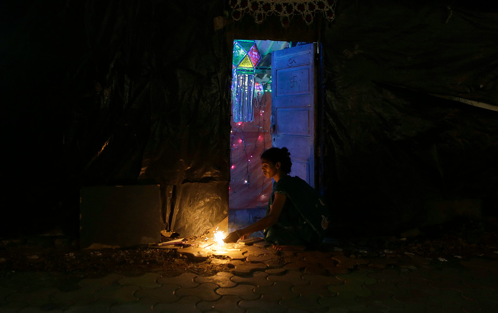 . A woman lights a firecrackers outside her house to celebrate Diwali, the Hindu festival of lights, in Mumbai India, Thursday, Oct. 19, 2017. (AP Photo/Rafiq Maqbool)