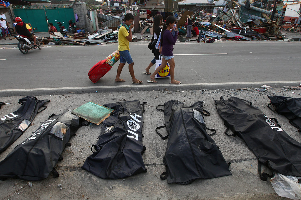 . People cover their noses from the stench of dead bodies in an area affected by Typhoon Haiyan in Tacloban, Philippines, Wednesday, Nov. 13, 2013. Typhoon Haiyan, one of the strongest storms on record, slammed into six central Philippine islands on Friday, leaving a wide swath of destruction. (AP Photo/Dita Alangkara)